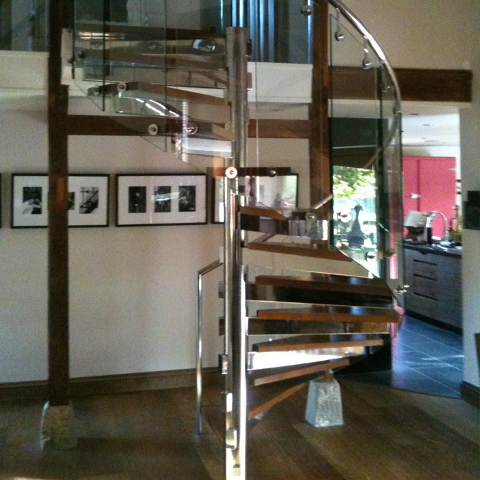 Stainless steel glass spiral staircase with oak timber treads.