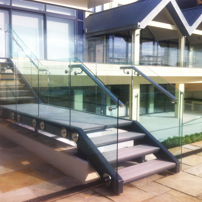 Contemporary mild steel exterior staircase with stainless steel handrails and structural glass balustrade.