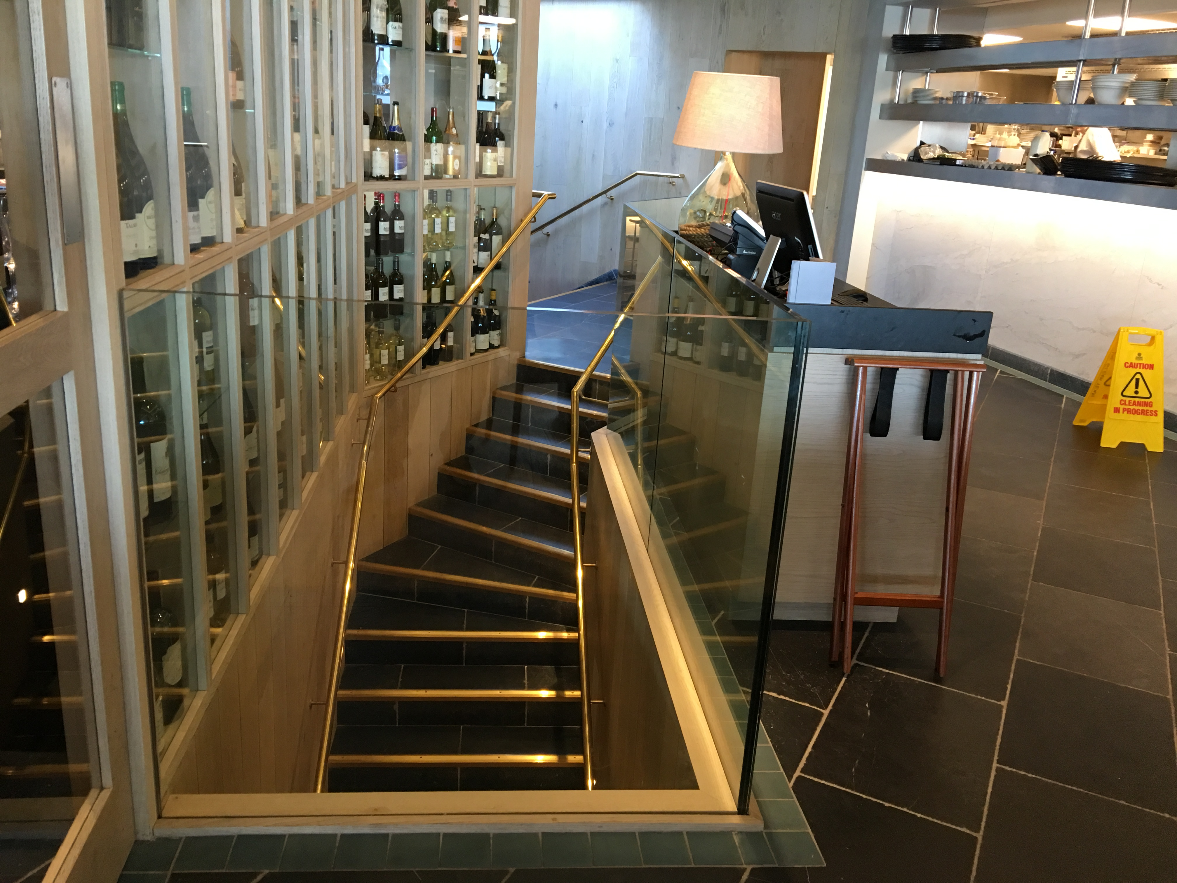 Mild steel staircase with brass handrails and structural glass balustrading.