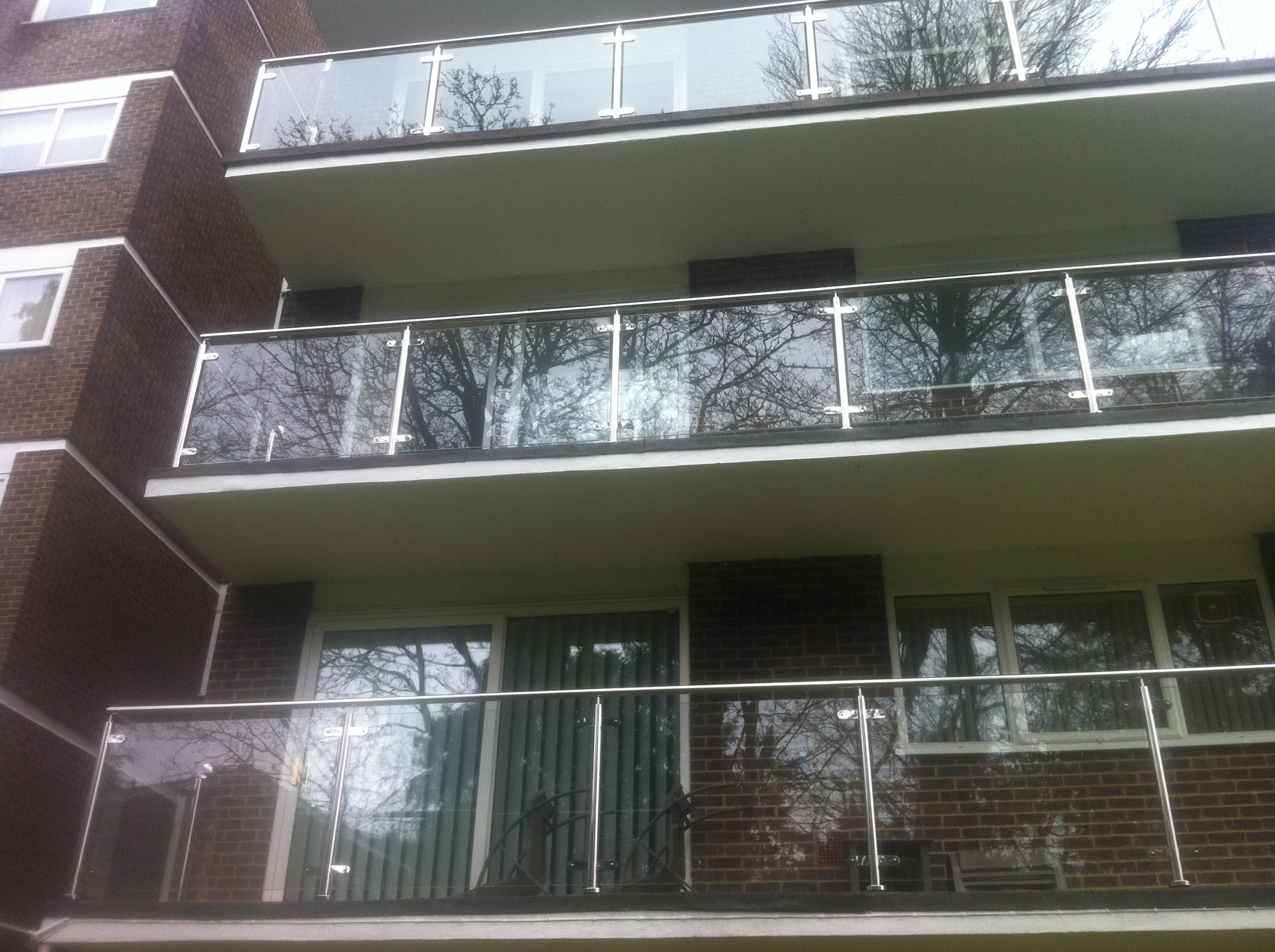 New stainless steel balustrades with glass infills to a large block of flats in Dorset.