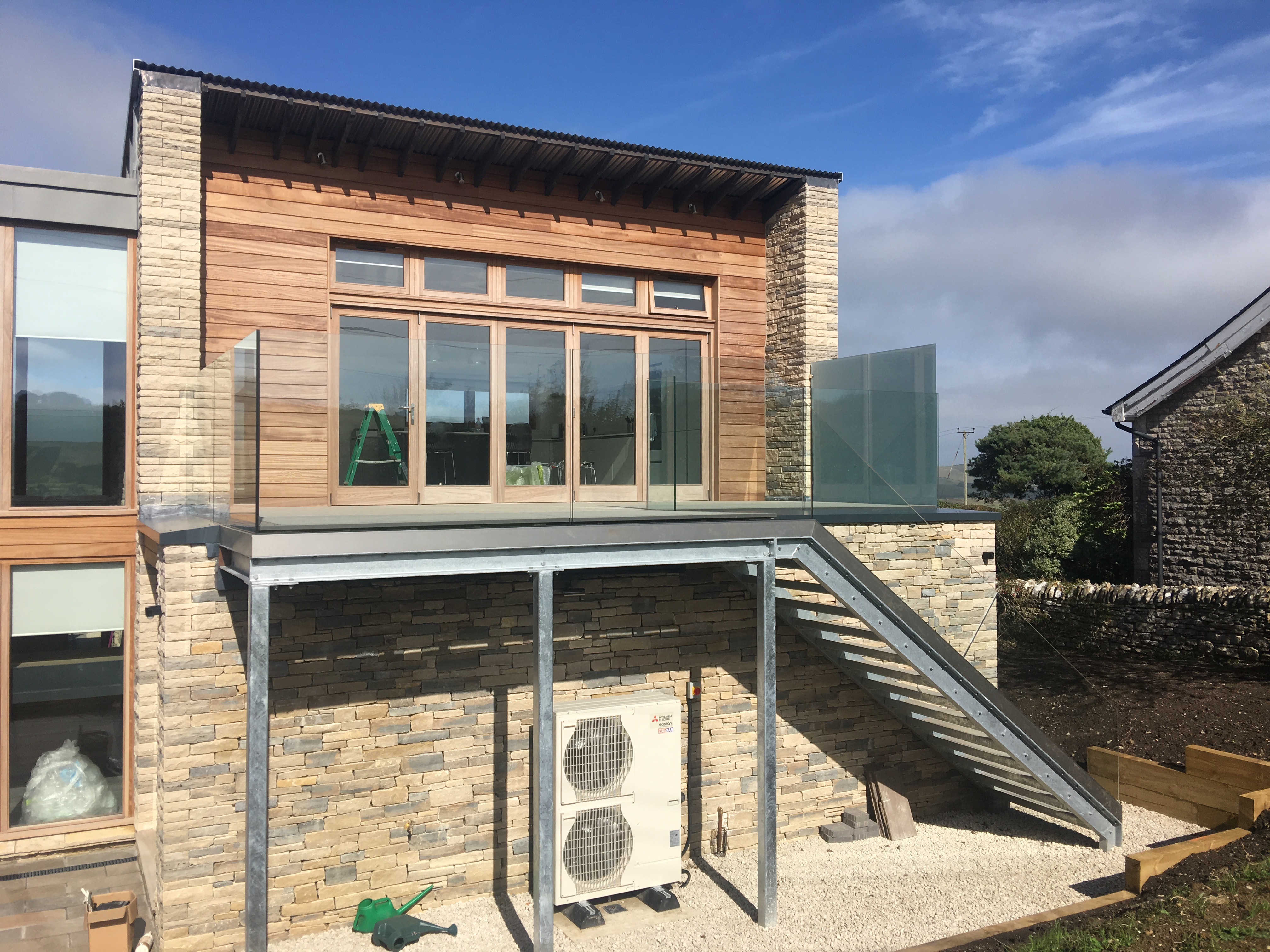 Contemporary exterior galvanised staircase with structural glass balustrading.